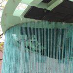 Befestigungspunkte des Stangenvorhangs und abgedichtete Leerräume vom Wolkenpavillon. Dabei muss darauf geachtet werden, dass das Kupfer sich bei Temperaturunterschieden wie Sommer und Winter, stark verändert, sodass eine Längsausdehnungsmöglichkeit von ca. 2-3 cm vorhanden sein muss. Das Kupferrohr ist oben mit einem 30 cm- Stahlrohr geschient, sodass diese Längsbeweglichkeit möglich wird.
